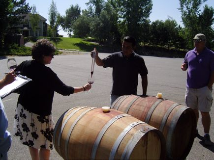 The assistant winemaker at Badger Mountain/Powers Winery uses a glass thief to distribute barrel samples.